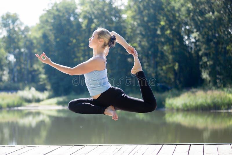Yogi женское делая Eka Pada Rajakapotasana в среднем воздухе стоковые фото