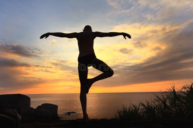 Yogi размышляя на заходе солнца стоковые изображения