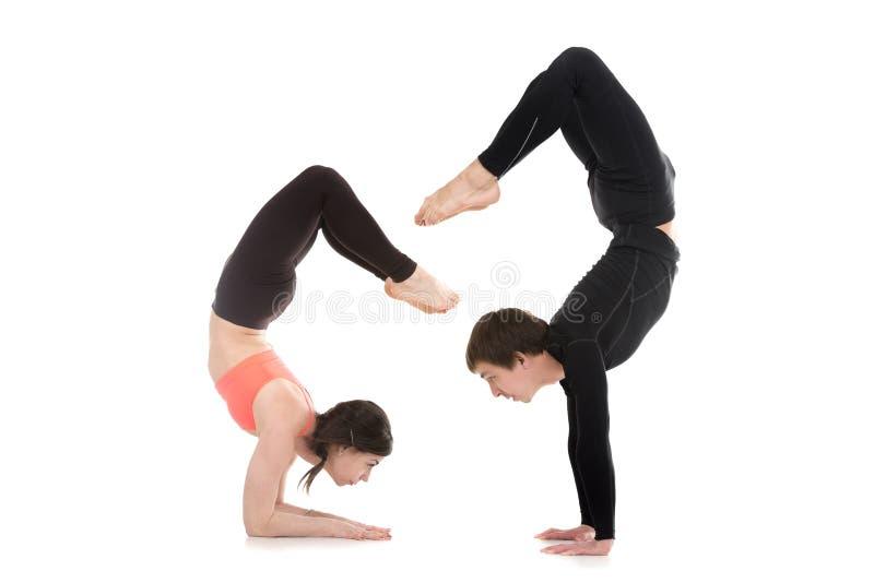 Yogi couple in yoga Scorpion Pose stock photo