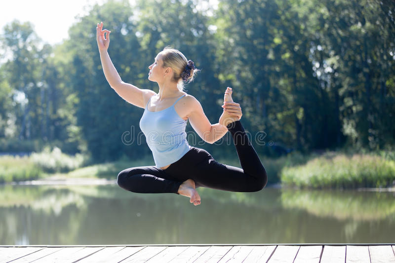 Yogi female doing One-legged king pigeon pose in mid air royalty free stock images
