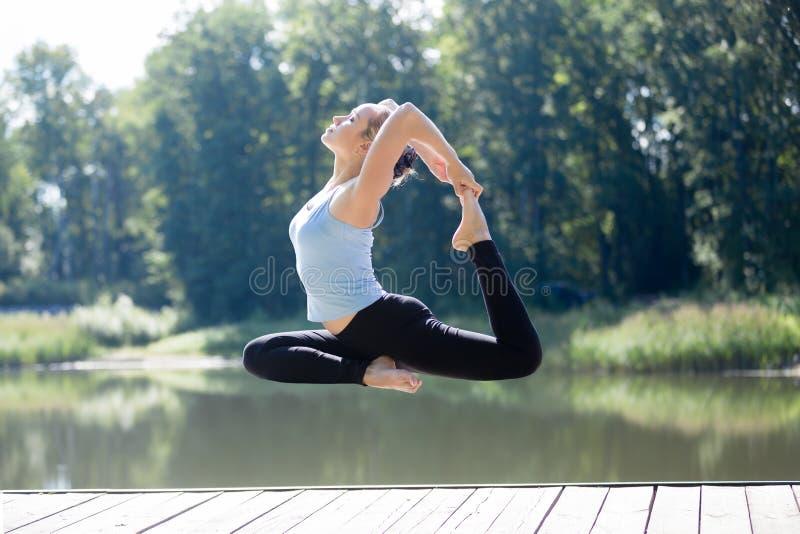 Yogi female doing Royal Pigeon pose in mid air royalty free stock photos