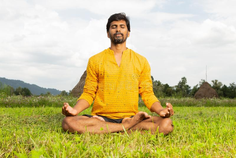 Yogi sitting in lotus pose stock image