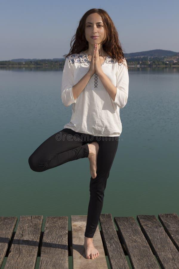 Yogi woman doing tree pose outdoors in nature royalty free stock photo