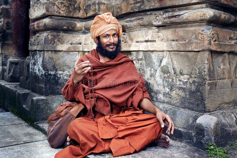 Yogin sitter nära templet royaltyfria bilder