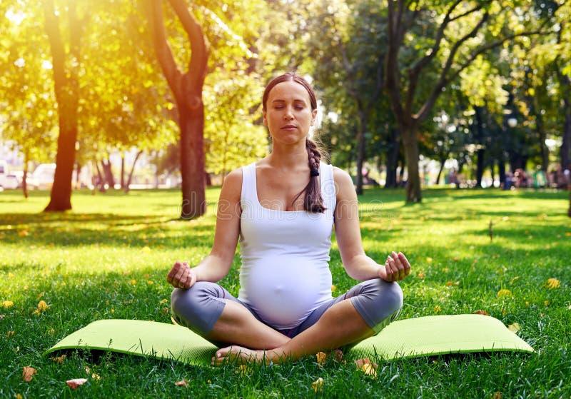 Yogini grávido concentrado que relaxa no parque fotos de stock royalty free