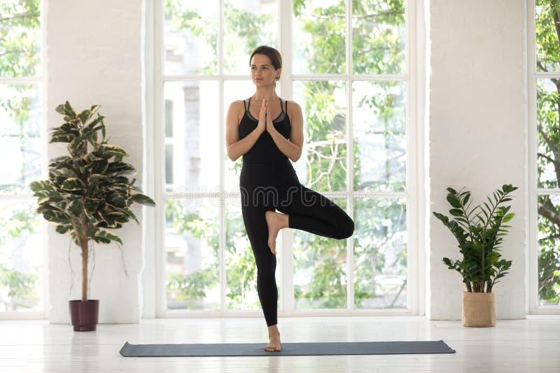 Yogini que a mulher bonita pratica a ioga executa o asana da pose da árvore dentro fotos de stock royalty free