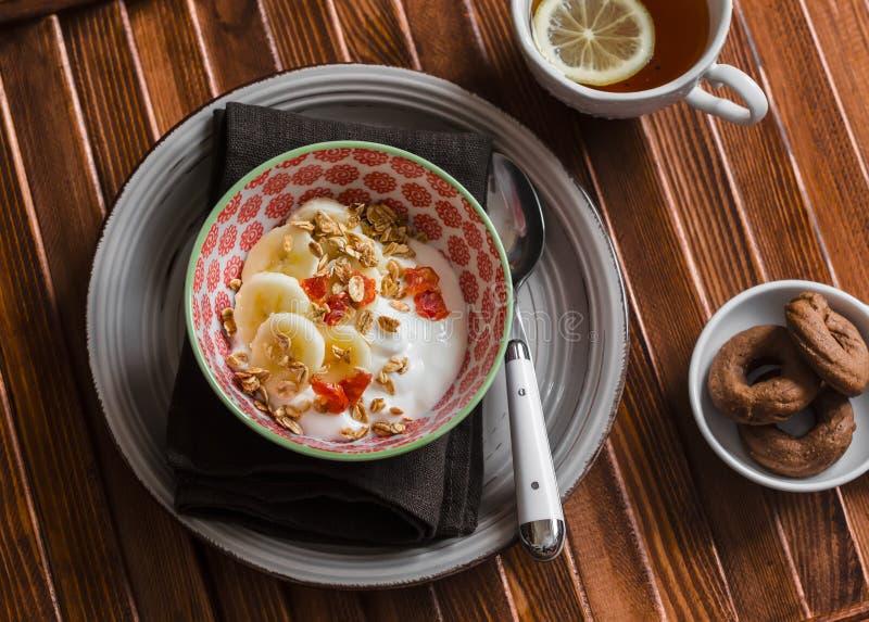 Yogur con el plátano, frutos secos y granola, galletas de microprocesador de chocolate y té con el limón en fondo de madera marró foto de archivo libre de regalías