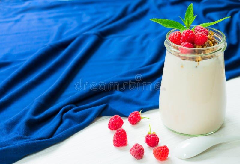 Yogur con las bayas de la frambuesa y muesli, adornado con las hojas de menta, en un tarro de cristal en una tabla blanca con un  imagen de archivo