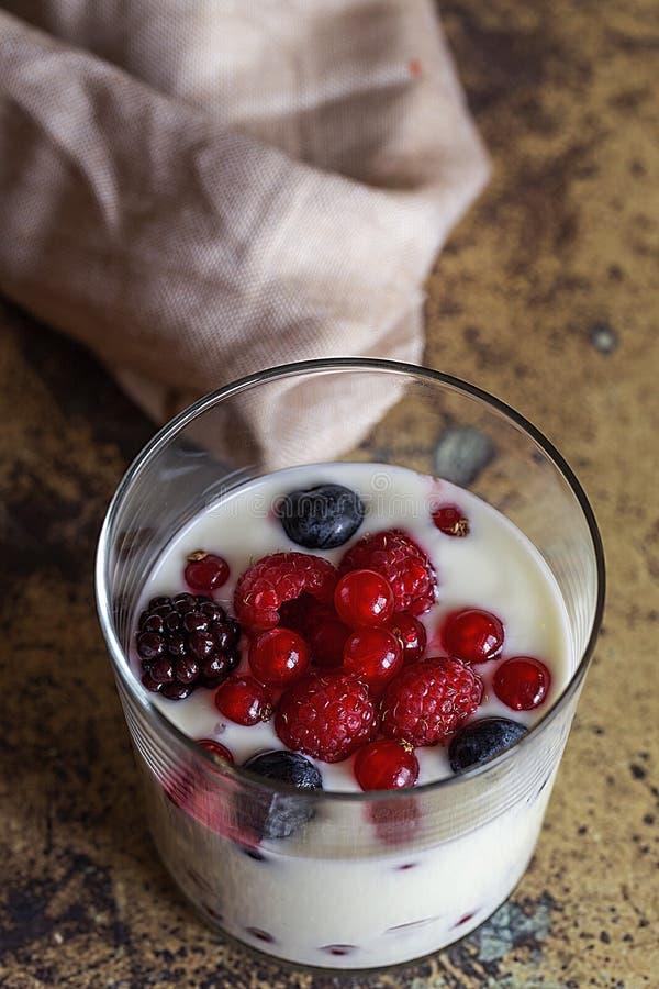 Yogur con las bayas, los arándanos y las frambuesas foto de archivo