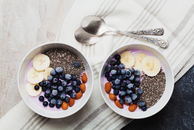 Yogur con las bayas, plátano, almendras y semillas de Chia, cuenco de desayuno sano cada mañana, estilo del vintage, superfood y  imágenes de archivo libres de regalías