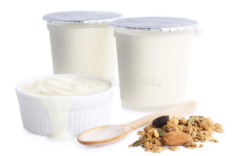 Yogur condimentado sano en taza plástica y cuenco de cerámica con el cer imagen de archivo