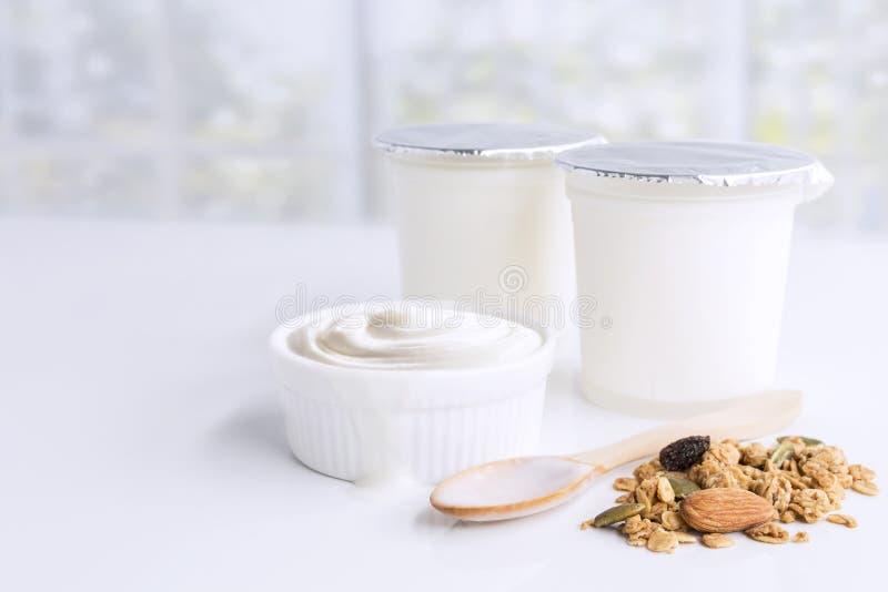 Yogur condimentado sano en taza plástica y cuenco de cerámica con el granola en cuchara de madera en la harpillera con en el fond foto de archivo libre de regalías