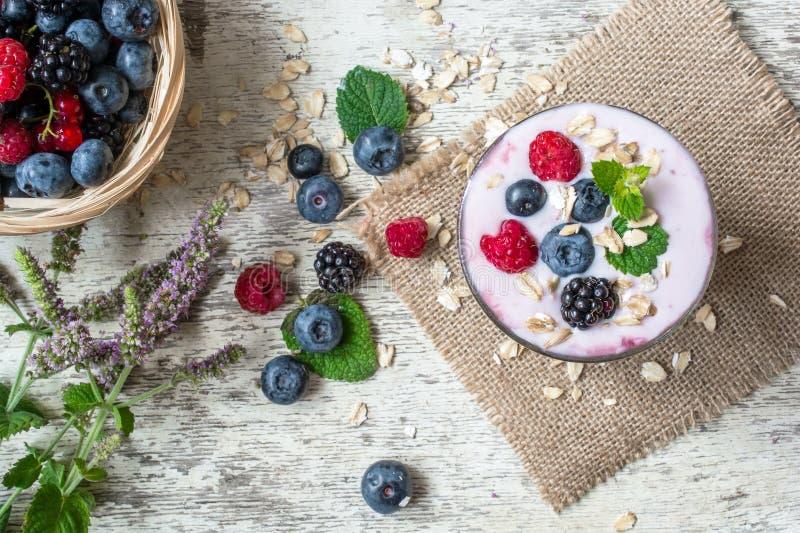 Yogur de fruta con las bayas y la menta en un vidrio Visión superior imagen de archivo libre de regalías