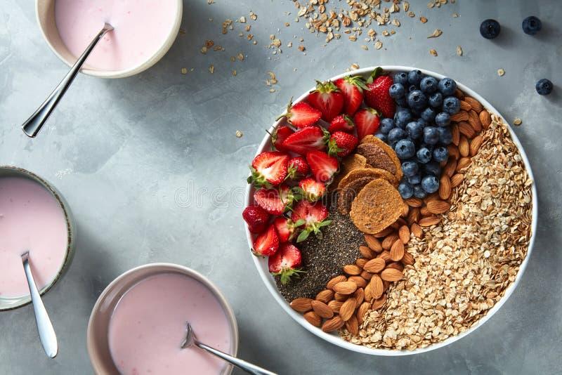 Yogur en vidrios con el granola, las bayas y las semillas del chia para el desayuno sano en un fondo concreto foto de archivo libre de regalías