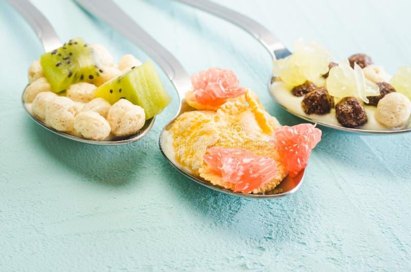 Yogur, escamas y fruta sanos del desayuno en cucharas en un fondo azul fotos de archivo