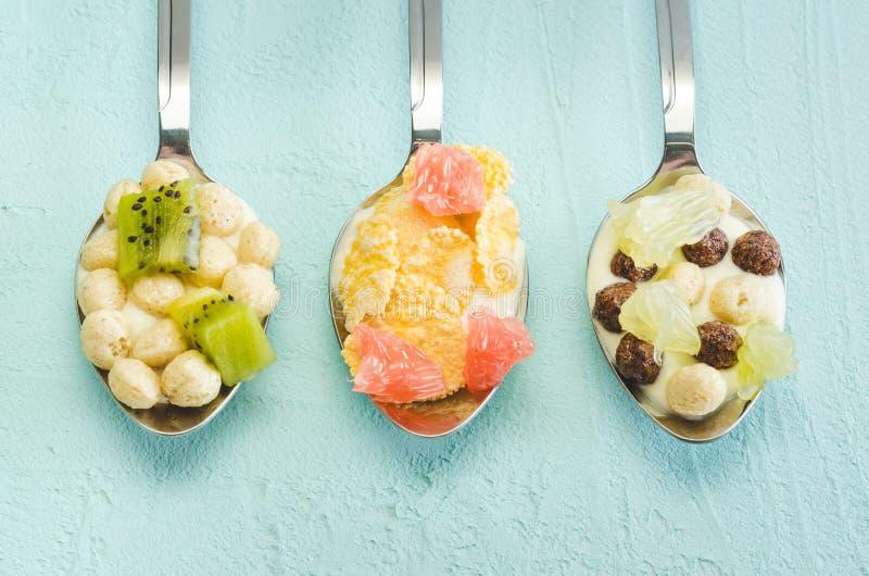 Yogur, escamas y fruta sanos del desayuno en cucharas en un fondo azul Visi?n superior, flatlay fotos de archivo