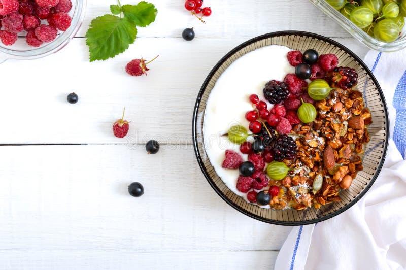 Yogur, granola, bayas frescas en un cuenco en un fondo de madera blanco Nutrición apropiada del desayuno delicioso y sano diet?ti fotos de archivo