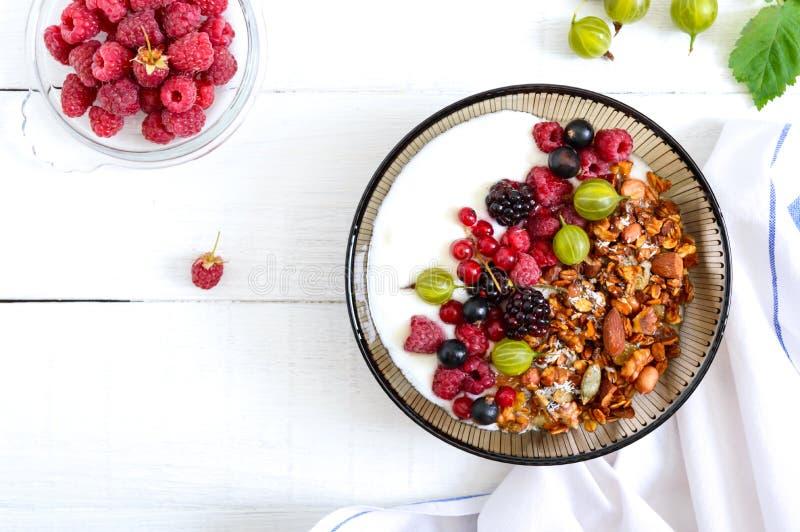 Yogur, granola, bayas frescas en un cuenco en un fondo de madera blanco Nutrición apropiada del desayuno delicioso y sano diet?ti imagen de archivo