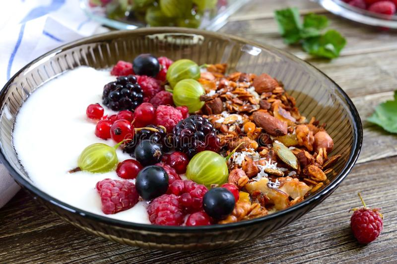 Yogur, granola, bayas frescas en un cuenco en una tabla de madera Nutrición apropiada del desayuno delicioso y sano Men? diet?tic imágenes de archivo libres de regalías