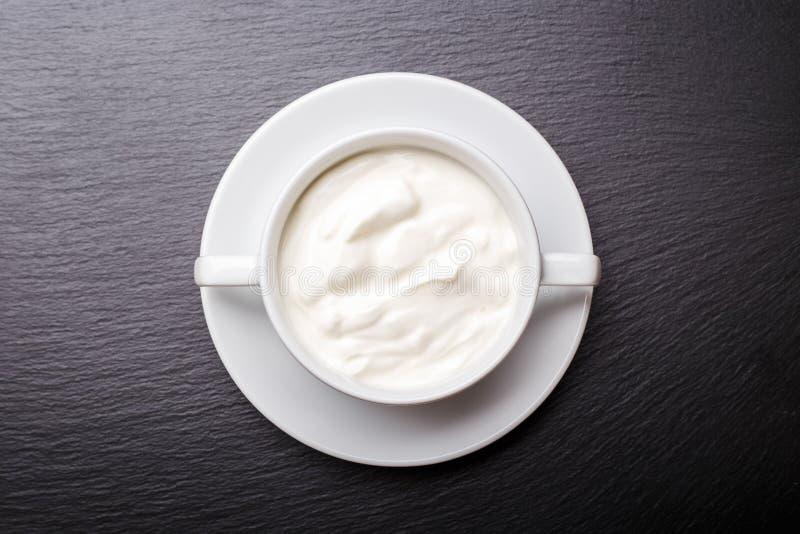 Yogur griego en el cuenco blanco en fondo negro de la pizarra con el espacio de la copia fotografía de archivo libre de regalías