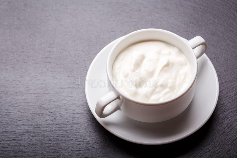 Yogur griego en el cuenco blanco en fondo negro de la pizarra con el espacio de la copia fotografía de archivo