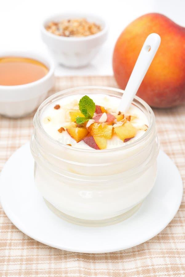 Yogur hecho en casa con la miel, los melocotones y las nueces en un tarro de cristal imagenes de archivo