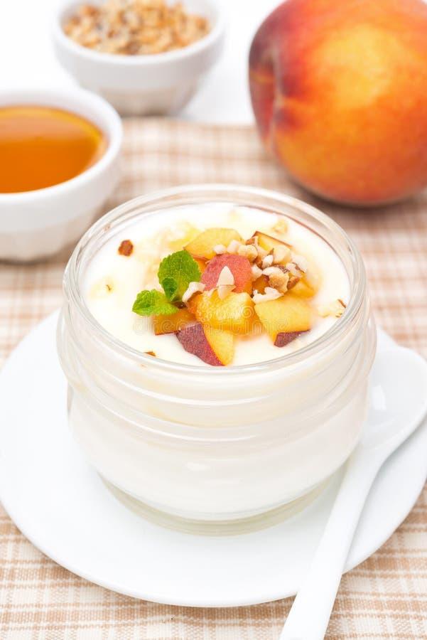 Yogur hecho en casa con la miel, los melocotones y las nueces, verticales imagen de archivo