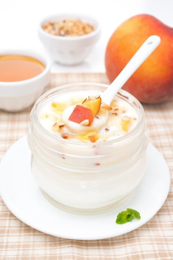 Yogur hecho en casa con la miel, melocotones, nueces en una cuchara imágenes de archivo libres de regalías
