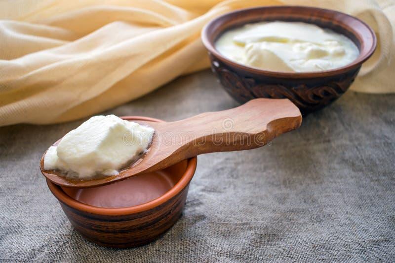 Yogur hecho en casa de la leche en una cuchara de madera sobre un cuenco de la arcilla de yog fotos de archivo