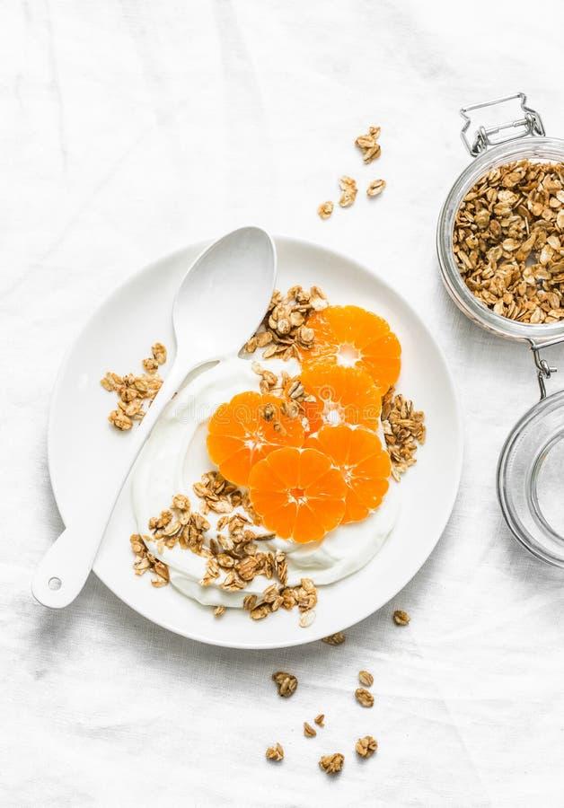Yogur hecho en casa del coco con el granola y las mandarinas en el fondo blanco El gluten libera fotos de archivo