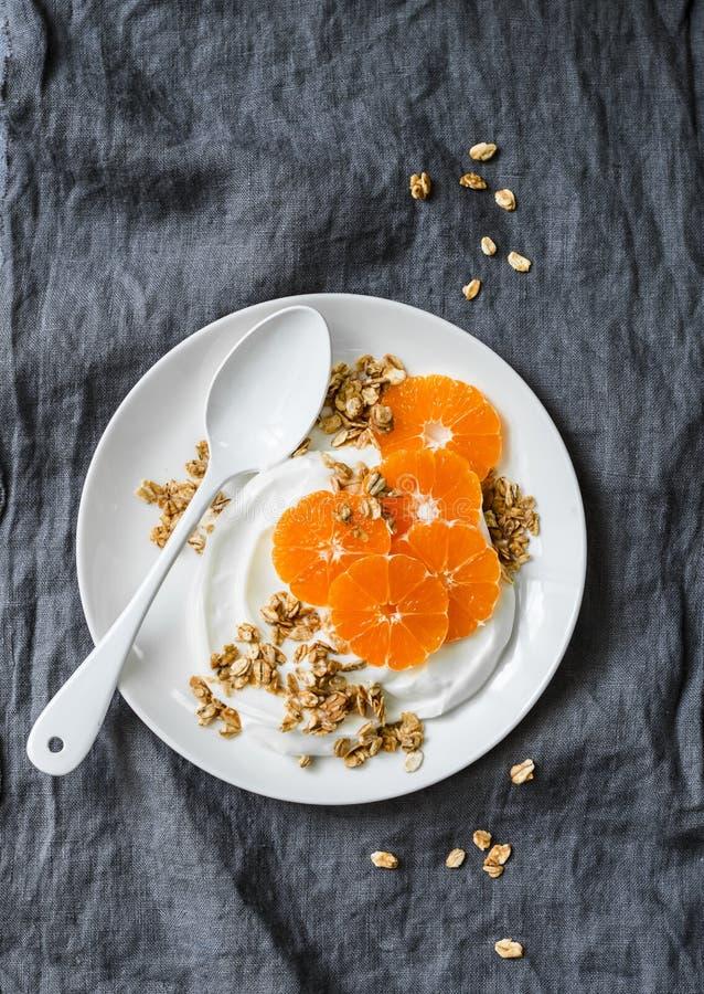 Yogur hecho en casa del coco con el granola y las mandarinas en fondo gris El gluten libera imagenes de archivo