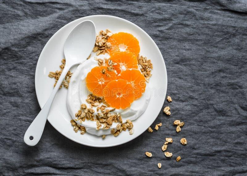 Yogur hecho en casa del coco con el granola y las mandarinas en fondo gris El gluten libera fotos de archivo