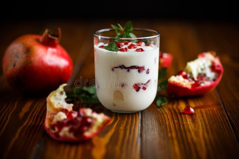 Yogur hecho en casa dulce con la granada imagen de archivo