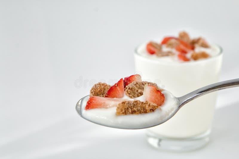 Yogur natural en una cuchara con las escamas de la fresa y del multigrain Visión superior imagenes de archivo