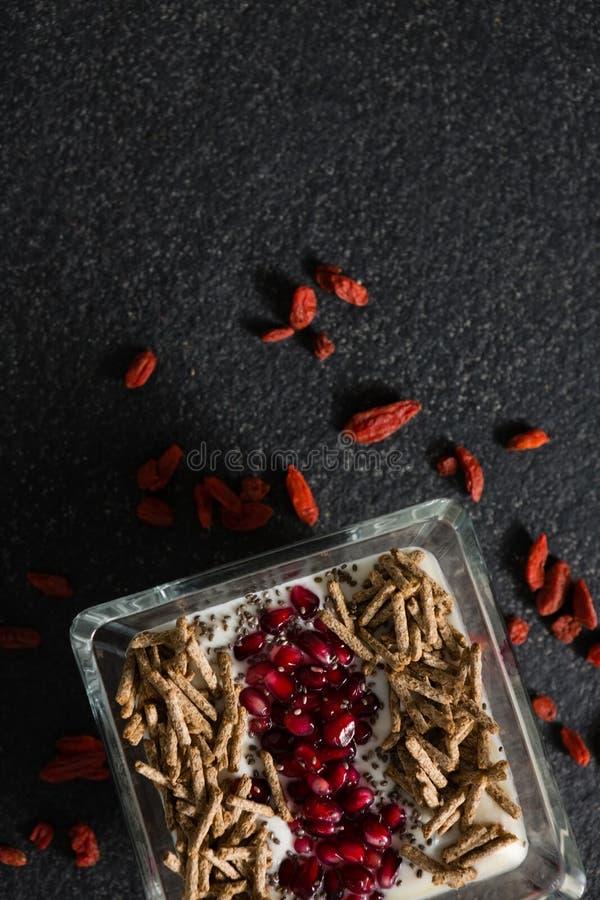 Yogur, palillos del salvado del cereal y semillas de la granada en bandeja con las frutas secadas foto de archivo