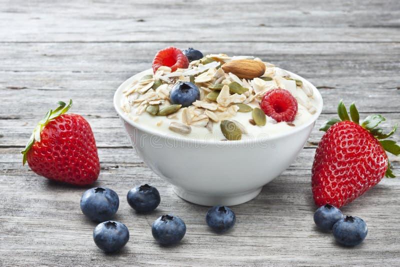 Yogurt Muesli Berries Food Background Breakfast. A bowl of yogurt sprinkled with muesli and berries on a rustic wood background stock photos