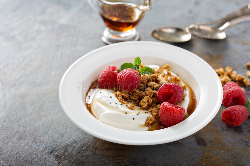 Yogurt bowl with raspberry and maple syrup. Yogurt bowl with granola, raspberry and maple syrup royalty free stock photo