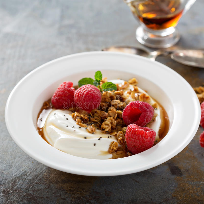 Yogurt bowl with raspberry and maple syrup. Yogurt bowl with granola, raspberry and maple syrup royalty free stock images