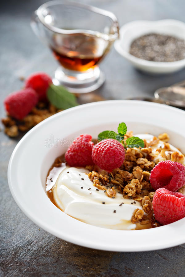 Yogurt bowl with raspberry and maple syrup. Yogurt bowl with granola, raspberry and maple syrup stock images