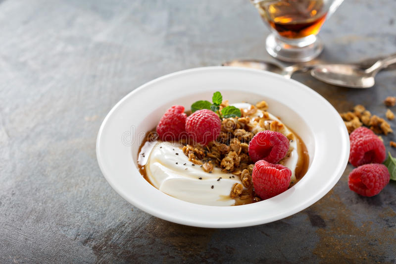 Yogurt bowl with raspberry and maple syrup. Yogurt bowl with granola, raspberry and maple syrup stock photo