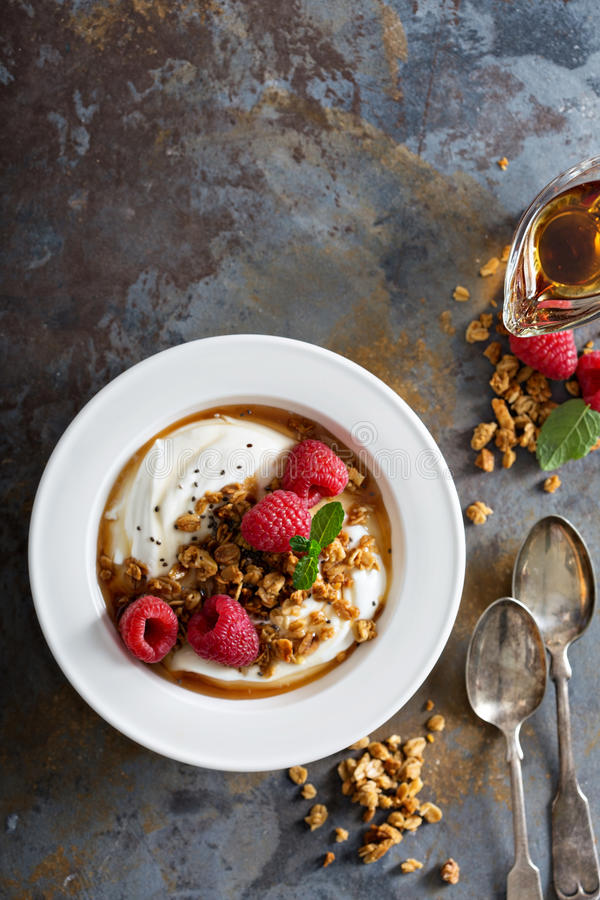 Yogurt bowl with raspberry and maple syrup. Yogurt bowl with granola, raspberry and maple syrup overhead shot royalty free stock photo