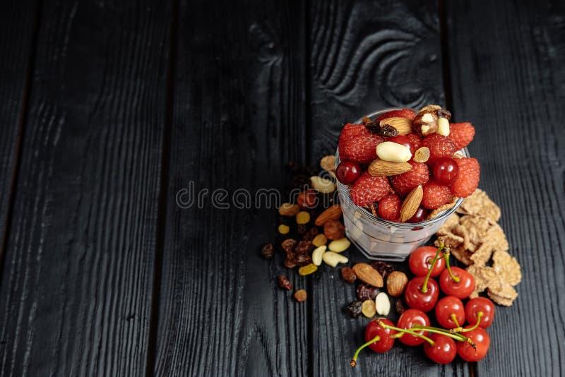 Yogurt casalingo con i fiocchi, i dadi e le bacche dei lamponi e delle ciliege fotografia stock