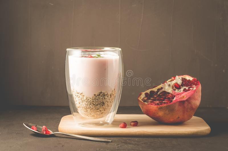 Yogurt. Yogurt with cereals, garnet and mint in glass and pomegranate fruit on a wooden tray. Dark backgtound table. Selective. Focus stock image