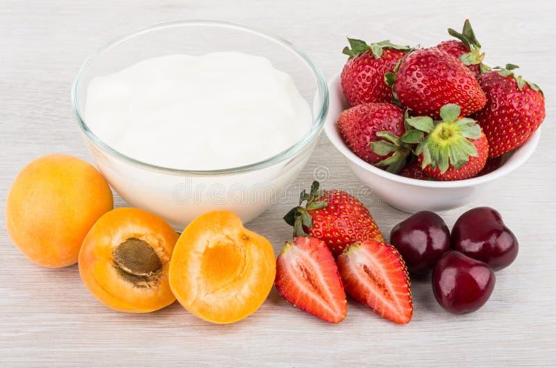 Yogurt, ciotola con le fragole, pezzi di albicocche e ciliege immagine stock libera da diritti