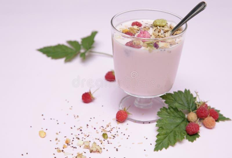 Yogurt con granola in un vetro con il cucchiaio ed i lamponi con le foglie su un fondo bianco con lo spazio della copia per testo fotografie stock
