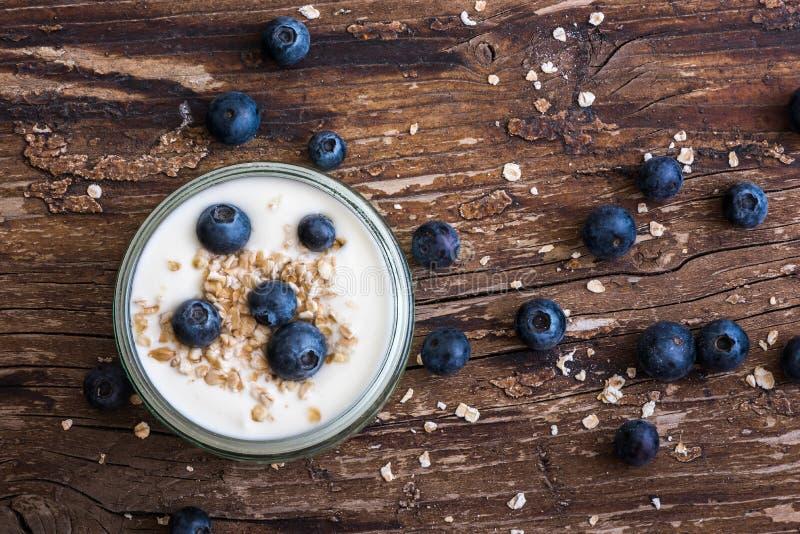 Yogurt con i mirtilli freschi sulla Tabella di Woden fotografia stock