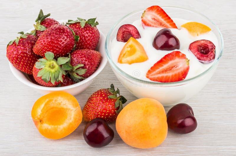 Yogurt con i pezzi, le ciliege e le fragole dell'albicocca fotografie stock libere da diritti