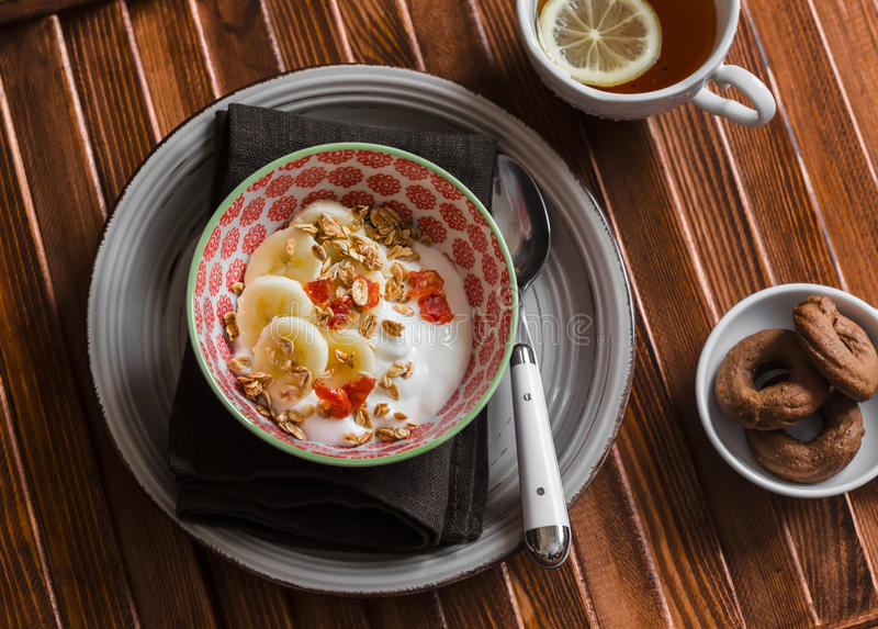 Yogurt con la banana, frutta secca e granola, biscotti di pepita di cioccolato e tè con il limone su fondo di legno marrone fotografia stock libera da diritti