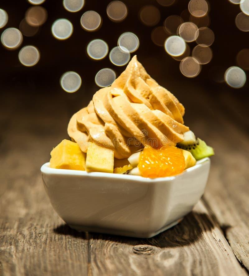 Yogurt congelato giallo sulle fette della frutta sulla ciotola bianca fotografie stock