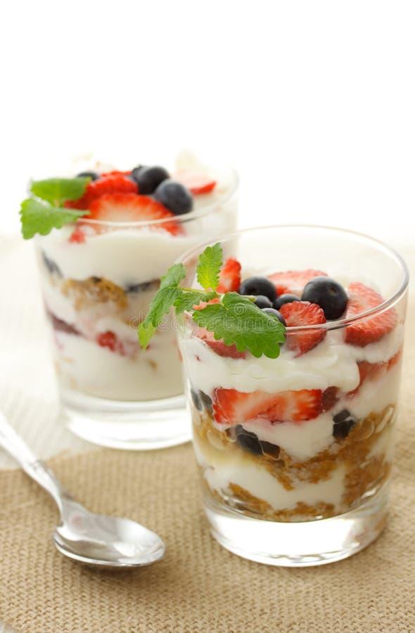 Yogurt della vaniglia sopra le fragole ed i mirtilli immagini stock libere da diritti